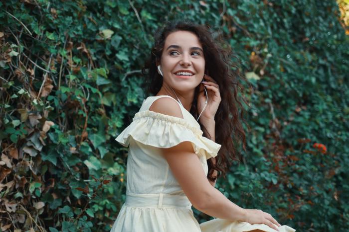 Młoda dziewczyna z pięknymi długimi kręconymi włosami siedząca w ogrodzie
