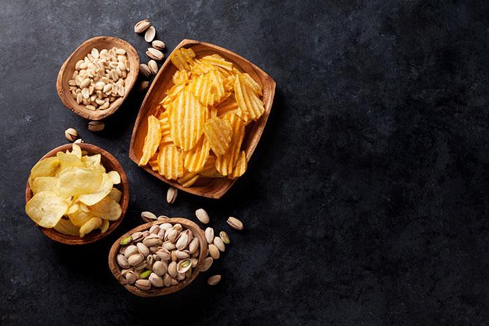 Miseczki z chipsami, orzeszkami i pistacjami na czarnym tle