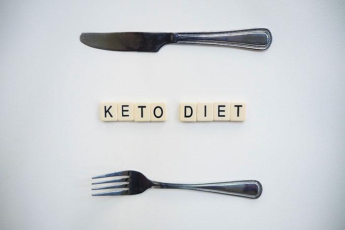 napis keto diet ułożony z kostek na jasnym tle, powyżej napisu znajduje się nóż a poniżej widelec