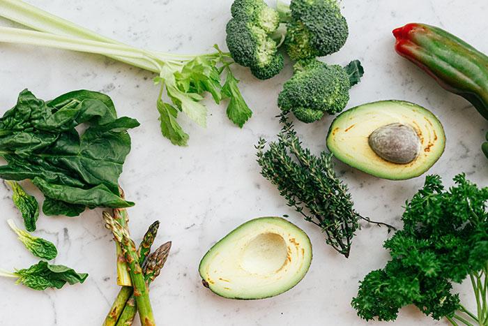 zielone warzywa ułożone na jasnym tle, awokado, brokuły, cukinia, szpinak, szparagi